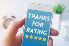 Thanks for rating message on smartphone screen. In male hand. Customer service survey feedback concept royalty free stock images