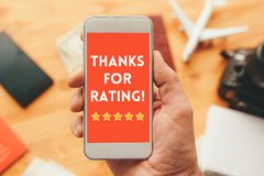 Thanks for rating message on smartphone screen. In male hand. Customer service survey feedback concept royalty free stock photos