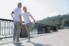Cheerful woman stretching with the help of husband Stock Images