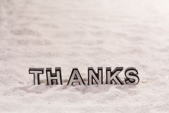 Thanks word on white sand. Thanks word silver and black on shiny white sand royalty free stock images