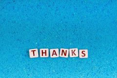 Thanks word on stone. Thanks word write in square white stone on blue sand, free space for your text Royalty Free Stock Images