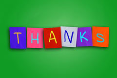 Thanks. The word thanks you written on sticky colored paper over cork board stock image