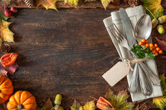 Thanksgiving autumn place setting. With cutlery and arrangement of colorful fall leaves Stock Image