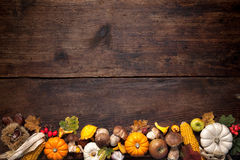 Thanksgiving background. Harvest or Thanksgiving background with autumnal fruits and gourds on a rustic wooden table