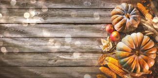 Thanksgiving background with pumpkins and falling leaves on rust. Thanksgiving background with pumpkins, corn cobs, wheat and falling leaves on rustic wooden stock image