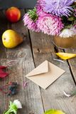 Thanksgiving background with seasonal fruits, flowers and craft paper envelope on a rustic wooden table. Autumn harvest concept. C Royalty Free Stock Photos