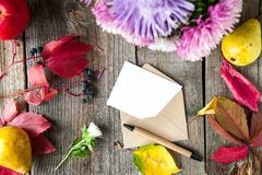 Thanksgiving background with seasonal fruits, flowers, greeting card and envelope on a rustic wooden table. Autumn harvest concept Stock Images