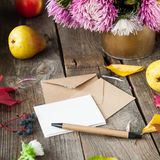 Thanksgiving background with seasonal fruits, flowers, greeting card and few craft envelopes on a rustic wooden table. Autumn harv Stock Photo