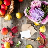 Thanksgiving background with seasonal fruits, flowers, greeting card, few craft envelopes on a rustic wooden table. Autumn harvest Royalty Free Stock Photos