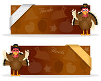 Thanksgiving Banners with Turkey. Two brown Thanksgiving Day banners with a cute cartoon turkey character smiling and greeting, autumnal elements and a ribbon Royalty Free Stock Photo