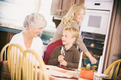 Thanksgiving: Boy And Grandmother Setting The Table. Traditional Thanksgiving holiday in the USA, with family preparing turkey and gathering around the table Royalty Free Stock Images