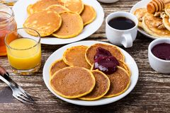 Thanksgiving brunch with pumpkin pancakes. Thanksgiving brunch with delicious pumpkin pancakes with berry jam, orange juice and cup of coffee stock images