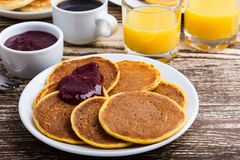 Thanksgiving brunch with pumpkin pancakes. Thanksgiving brunch with  delicious pumpkin pancakes with berry jam, orange juice and cup of coffee Royalty Free Stock Image