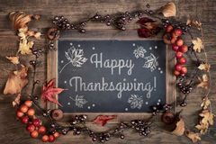 Thanksgiving card design with chalkboard and Autumn decorations. Blackboard with greeting `Happy Thanksgiving` with Autumn decorations on wood. Top view, toned Royalty Free Stock Photos