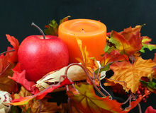 Thanksgiving Centerpiece. Apple, corn husks, leaves and candle representing harvest or thanksgiving stock photo