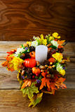Thanksgiving  centerpiece with candle and artificial fall leaves Royalty Free Stock Photography