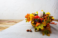 Thanksgiving centerpiece with white candle and silk fall leaves Stock Photography