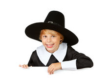 Thanksgiving: Cheerful Pilgrim Behind White Card. Series with children dressed in costume to celebrate the American Thanksgiving holiday.  Boy as pigrim, girl as Stock Image