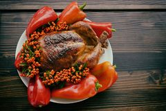 Thanksgiving or Christmas Background of  Holiday Turkey. On the Plate with Peppers and Berries on a Wooden Table Royalty Free Stock Photo