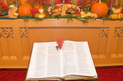 Thanksgiving church altar. A view of a Thanksgiving church altar decorated with harvest vegetables and breads and ann open Bible in the foreground Royalty Free Stock Images