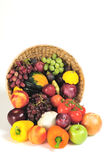 Thanksgiving cornucopia. A rich bounty of autumn harvest foods spilling from a basket Royalty Free Stock Images