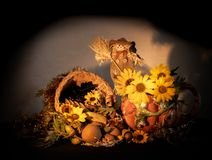 Thanksgiving cornucopia centerpiece with porcelain pumpkin pitcher, scarecrow, sunflowers and oak leaves celebrating fall autumn h royalty free stock photos