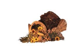Thanksgiving cornucopia centerpiece with sunflowers, turkey and turkey feathers, oak leaves, celebrating fall autumn harvest holid. Thanksgiving cornucopia royalty free stock photo