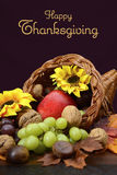 Thanksgiving Cornucopia Centerpiece. Thanksgiving cornucopia, wicker horn of plenty, centerpiece with fruit, nuts, leaves and sunflowers on dark wood table Stock Image