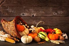 Thanksgiving cornucopia filled with autumn pumpkins and vegetables against dark wood