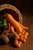 Thanksgiving cornucopia with fruits and vegetables. Thanksgiving cornucopia filled with autumn fruits and vegetables on wooden table Stock Photos