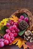 Thanksgiving cornucopia on wood background. Autumn background with traditional Thanksgiving cornucopia on dark wood table Stock Image