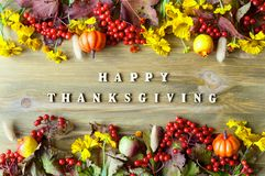 Thanksgiving day autumn background with with Happy Thanksgiving letters, seasonal autumn berries, pumpkins, apples stock photography