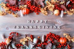 Thanksgiving day autumn background with with Happy Thanksgiving letters, seasonal autumn berries, pumpkins, apples royalty free stock images