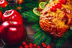 Christmas table dinner time with roasted meats, candles and New Year décor. Background thanksgiving day. Royalty Free Stock Images