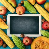Thanksgiving day concept. Blank chalk board with apples, pears, pumpkin, nuts and bitter melon on wooden background, top view Royalty Free Stock Photo