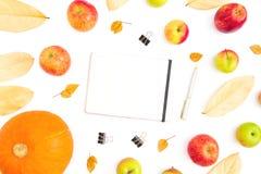 Thanksgiving day De herfstsamenstelling van dalingsbladeren, appelfruit en pompoen met notitieboekje, pen en klemmen op witte ach stock foto's