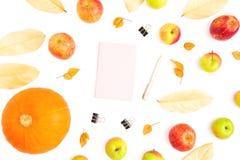 Thanksgiving day De herfstsamenstelling van dalingsbladeren, appelvruchten en pompoen met roze agenda, pen en klemmen op witte ac stock foto's