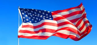 US flag flies in the blue sky to the wind of freedom. On Thanksgiving Day the flag of the United States of America flies with the wind of freedom in the blue sky royalty free stock photo
