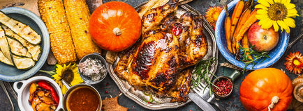 Thanksgiving Day food. Various grilled vegetables ,roasted chicken or turkey and pumpkin with sunflowers decoration on dark backgr Royalty Free Stock Images