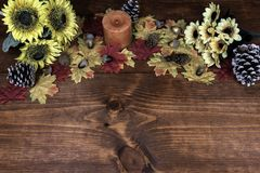 Thanksgiving decor with candle, frosted pine cones, sunflowers, acorns and maple leaves. stock photography