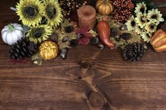 Thanksgiving decor with candle, pine cones, sunflowers, acorns, pumpkins, squash, guard, berries and maple leaves. royalty free stock photography