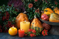 Thanksgiving decor with candle and pumpkins. Autumn thanksgiving decor at home with a candles, pumpkins and autumn flowers Royalty Free Stock Image