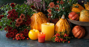 Thanksgiving decor with flowers and candle. Autumn decor at home with a candles, pumpkins and autumn flowers Royalty Free Stock Photos