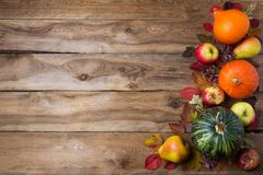 Thanksgiving decor with green pumpkin, orange onion squash, fall leaves, apples and pears on the rustic wooden background, copy stock photography