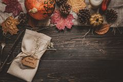 Thanksgiving decoration with cutlery and napkin on the wooden table, top view. Copy space.  Stock Image