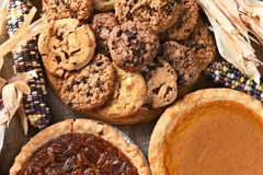 Thanksgiving Desserts. Closeup of pies and cookies for a Thanksgiving Day feast desserts. Pecan Pie, Pumpkin Pie, Chocolate Chip, oatmeal raisin and indian corn Royalty Free Stock Images