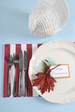 Thanksgiving dining table place setting in modern pale blue, red and white theme - vertical. Royalty Free Stock Photos