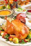 Thanksgiving dinner. With roast turkey, baked ham, pumpkin pie, gravy, dinner rolls, cranberry chutney etc royalty free stock photos