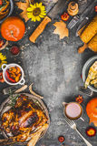Thanksgiving dinner cooking preparation with various traditional dishes: turkey,pumpkin, corn,sauce and roasted harvest vegetables. On rustic background, top stock images