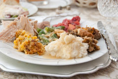 Thanksgiving Dinner Plate. A dinner plate of traditional Thanksgiving Day foods is set. The foods include turkey, dressing, mashed potatoes with gravy, a green Stock Photos